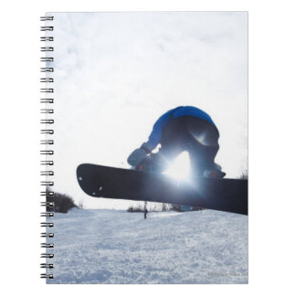 A female snowboarder takes air in New Hampshire. Notebook