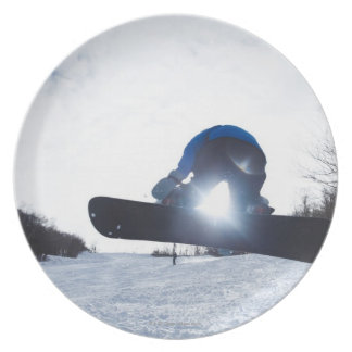 A female snowboarder takes air in New Hampshire. Plate