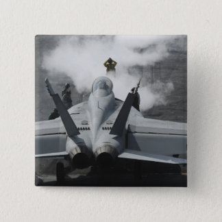 A flight deck director signals an F/A-18F 15 Cm Square Badge