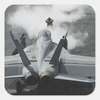 A flight deck director signals an F/A-18F Square Sticker