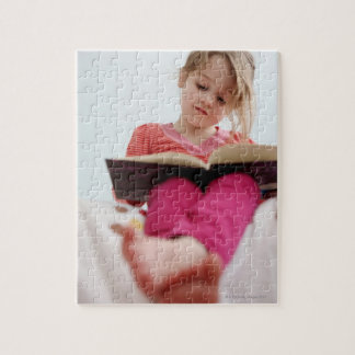 A four-year-old girl reads a book while sitting jigsaw puzzle