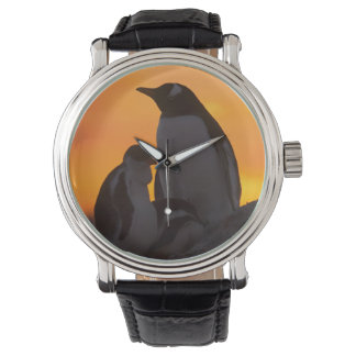 A gentoo penguin adult and chick are silhouetted wristwatch