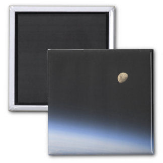 A gibbous moon visible above Earth s atmosphere Refrigerator Magnet
