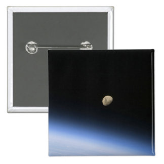A gibbous moon visible above Earth's atmosphere 2 Pinback Buttons