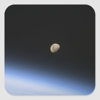 A gibbous moon visible above Earth's atmosphere 2 Square Sticker