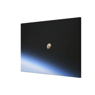 A gibbous moon visible above Earth's atmosphere Canvas Print