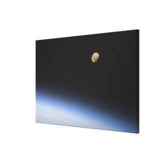 A gibbous moon visible above Earth's atmosphere Stretched Canvas Prints