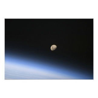 A gibbous moon visible above Earth's atmosphere Photo