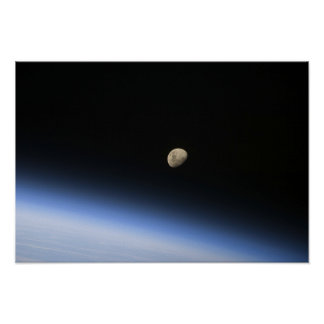 A gibbous moon visible above Earth's atmosphere Poster