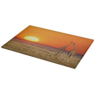 A Giraffe couple walks into the sunset, in Cutting Board