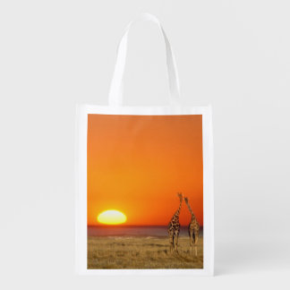 A Giraffe couple walks into the sunset, in Reusable Grocery Bag