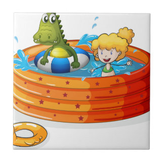 A girl and a crocodile swimming inside the inflata small square tile