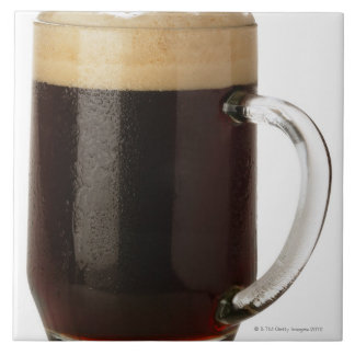 A glass of dark beer large square tile
