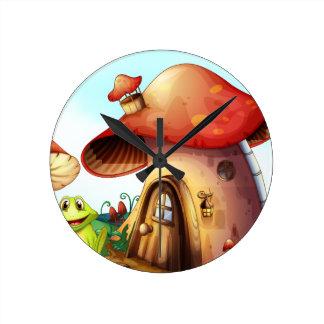 A green frog near a mushroom house round clock