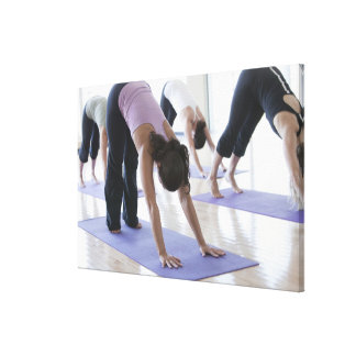 a group of women practicing yoga in a bright stretched canvas prints