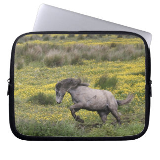 A horse running in a field of yellow wildflowers laptop sleeve