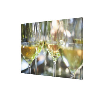 A host pours glasses of torrontes for guests at canvas print