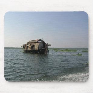 A houseboat moving placidly through a coastal lake mouse mat