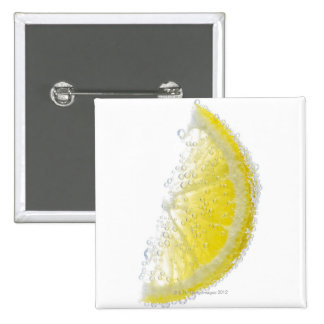 A juicy ripe organic lemon wedge fruit submerged 15 cm square badge