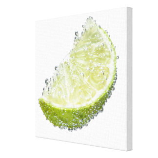 A juicy ripe organic lime wedge fruit submerged canvas print