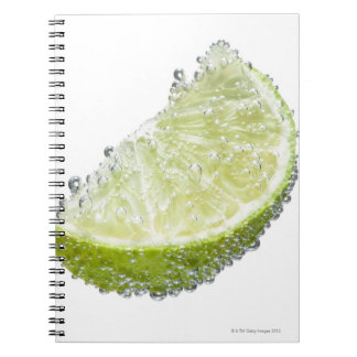A juicy ripe organic lime wedge fruit submerged notebooks