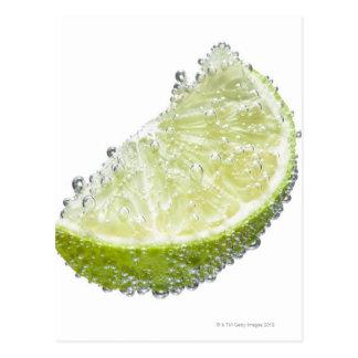 A juicy ripe organic lime wedge fruit submerged postcard