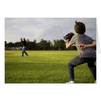 A kid wearing a baseball glove waits for his dad card