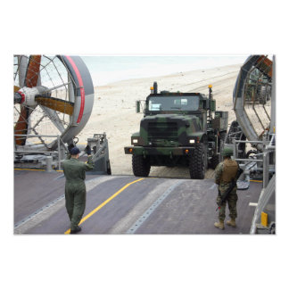 A loadmaster guides a Marine 7-ton truck Art Photo
