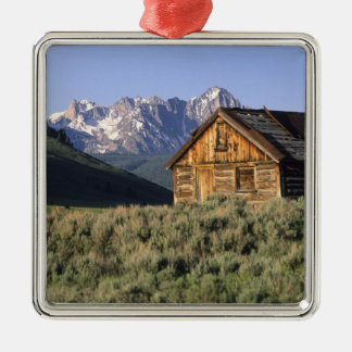 A log cabin and the Sawtooth Mountains in Silver-Colored Square Decoration