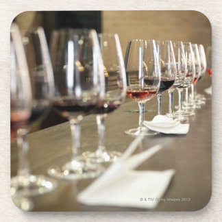 A long row of wine glasses set up so a large coaster