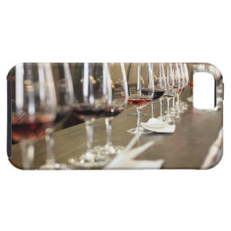 A long row of wine glasses set up so a large iPhone 5 covers