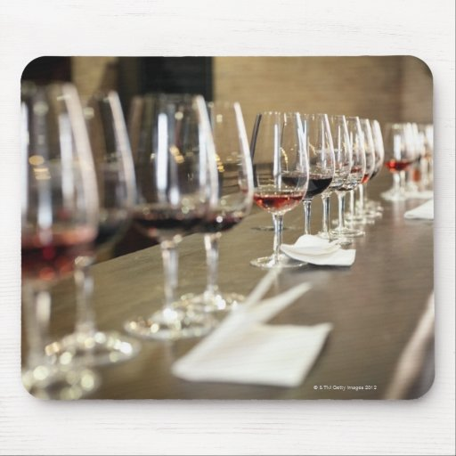 A long row of wine glasses set up so a large mousepads