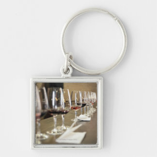 A long row of wine glasses set up so a large Silver-Colored square key ring
