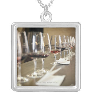 A long row of wine glasses set up so a large silver plated necklace