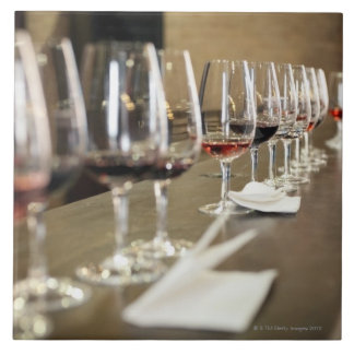 A long row of wine glasses set up so a large tile