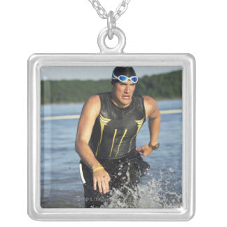 A male athelete running out of the water while 2 silver plated necklace