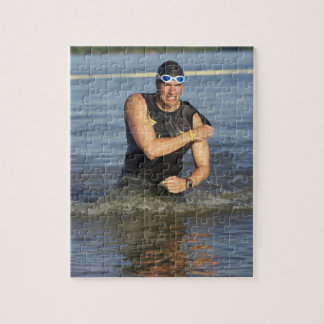 A male athelete running out of the water while jigsaw puzzle