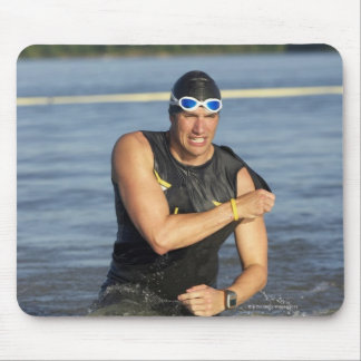 A male athelete running out of the water while mouse pad