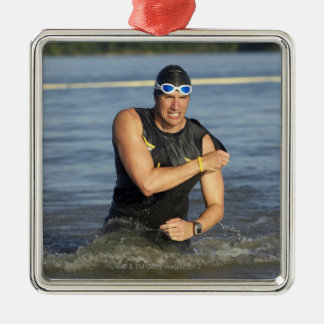 A male athelete running out of the water while Silver-Colored square decoration
