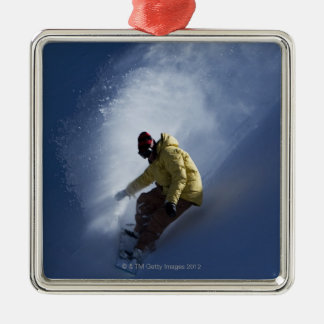 A male snowboarder catches last light on a christmas ornament