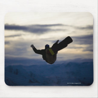 A male snowboarder does a back flip while riding mouse mat