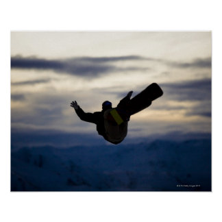 A male snowboarder does a back flip while riding posters