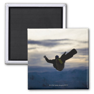 A male snowboarder does a back flip while riding square magnet