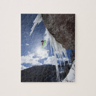 A male snowboarder jumps off an ice waterfall jigsaw puzzle