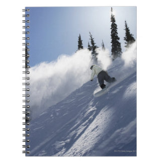 A male snowboarder ripping powder in Idaho. Spiral Notebook