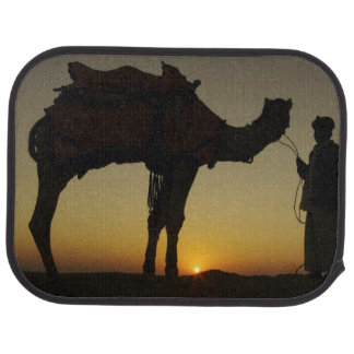 a man and his camel Silhouetted at sunset on the Car Mat