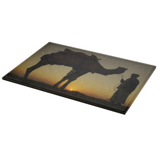 a man and his camel Silhouetted at sunset on the Cutting Board