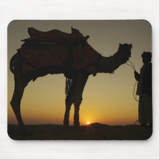 a man and his camel Silhouetted at sunset on the Mouse Mat