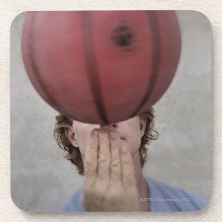 A man spinning a basketball ball on his finger coaster