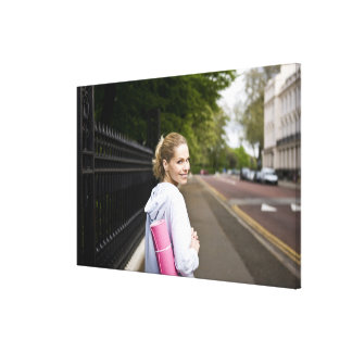 A mid adult woman carrying a yoga mat, walking canvas print